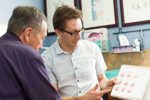 Denturist and patient discussing denture treatment options during a consultation appointment